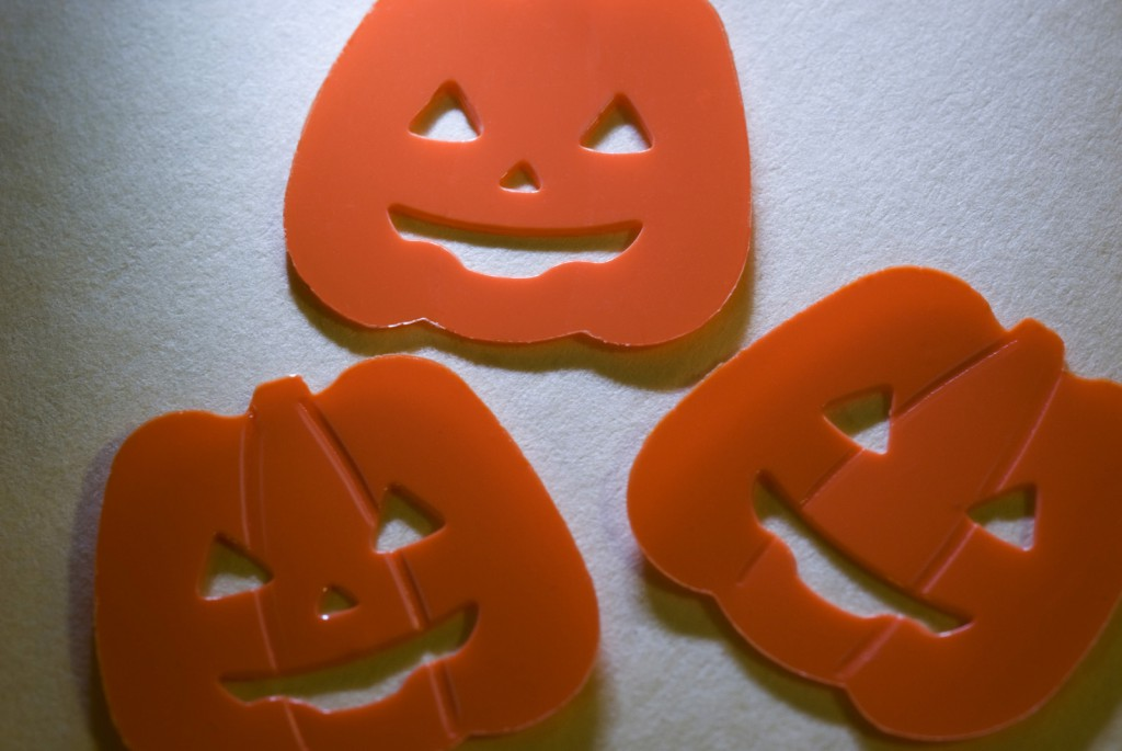 jack-o-lantern halloween shapes with smiles, lit with angled light from above